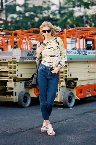 gelbes Mit Batikmuster Langarmshirt, dunkelblaue Jeans, weiße flache Sandalen aus Leder, schwarze Leder Umhängetasche für Damen