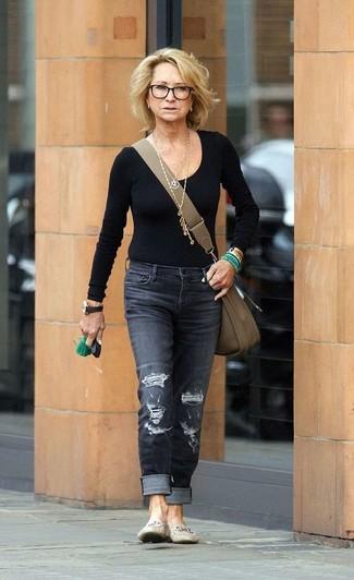 Felicity Kendal trägt schwarzes Langarmshirt, dunkelgraue Jeans mit Destroyed-Effekten, hellbeige Leder Slipper, olivgrüne Leder Umhängetasche