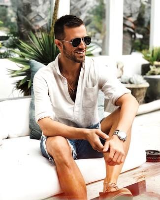 Wie kombinieren: hellbeige Langarmshirt mit einer Knopfleiste, blaue Jeansshorts mit Destroyed-Effekten, braune Leder Bootsschuhe, schwarze Sonnenbrille