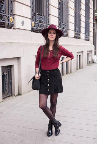 Wie kombinieren: dunkelrotes Langarmshirt, schwarzer Rock mit Knöpfen, schwarze Leder Stiefeletten, schwarze Leder Umhängetasche