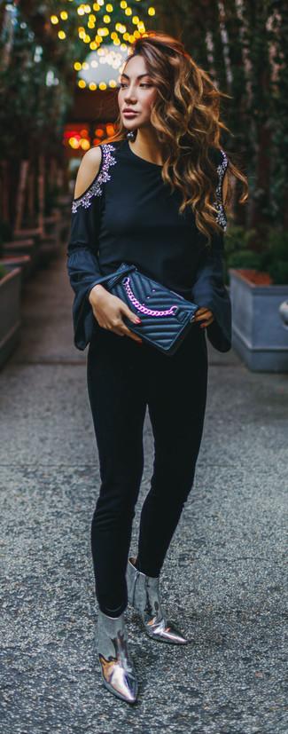 Wie kombinieren: schwarzes verziertes Langarmshirt, schwarze enge Hose, silberne Leder Stiefeletten, schwarze gesteppte Leder Clutch