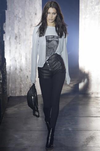 Schwarze Ledershorts kombinieren: trends 2020: Erwägen Sie das Tragen von einem weißen und schwarzen bedruckten Langarmshirt und schwarzen Ledershorts, um eine gemütliche Atmosphäre zu verleihen. Schwarze Leder Stiefeletten fügen sich nahtlos in einer Vielzahl von Outfits ein.