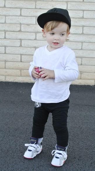 Wie kombinieren: weißes Langarmshirt, schwarze Jogginghose, weiße Turnschuhe, schwarze Baseballkappe