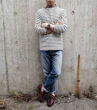 Teenager: Outfits Herren 2020: Ein weißes und dunkelblaues horizontal gestreiftes Langarmshirt und blaue Jeans sind eine perfekte Outfit-Formel für Ihre Sammlung. Fühlen Sie sich ideenreich? Vervollständigen Sie Ihr Outfit mit dunkelroten Leder Bootsschuhen.