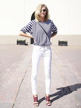 Wie kombinieren: weißes und dunkelblaues horizontal gestreiftes Langarmshirt, weiße Jeans, dunkelrote Leder Sandaletten, schwarze Leder Umhängetasche