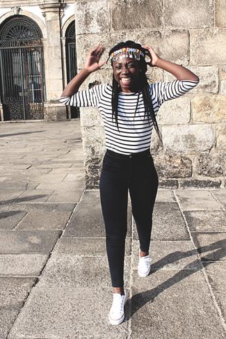 Wie kombinieren: weißes und schwarzes horizontal gestreiftes Langarmshirt, schwarze enge Jeans, weiße Segeltuch niedrige Sneakers, mehrfarbiges Haarband