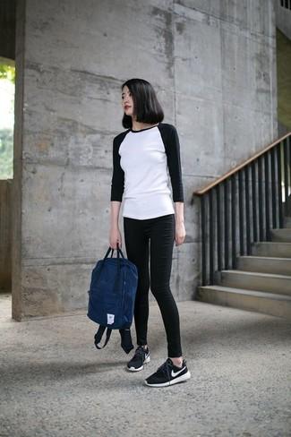 Wie kombinieren: weißes und schwarzes Langarmshirt, schwarze enge Jeans, schwarze und weiße Sportschuhe, dunkelblauer Rucksack