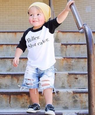 Wie kombinieren: weißes und schwarzes Langarmshirt, hellblaue Jeansshorts, schwarze Turnschuhe, gelbe Mütze