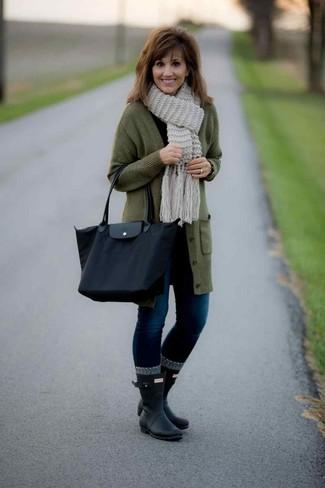 Wie kombinieren: olivgrüner lange Strickjacke, schwarzes Langarmshirt, dunkelblaue enge Jeans, schwarze Gummistiefel
