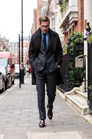 Wie kombinieren: dunkelgrauer Mantel, dunkelgrauer Wollanzug, blaues Chambray Businesshemd, dunkelbraune Doppelmonks aus Leder