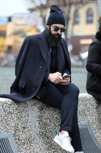 Wie kombinieren: schwarzer Mantel, schwarzer Anzug, weiße Leder niedrige Sneakers, schwarze Mütze