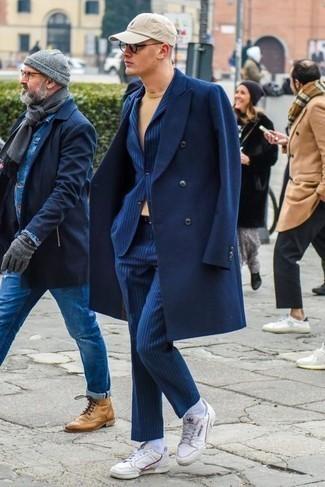 Blauen vertikal gestreiften Anzug kombinieren: trends 2020: Tragen Sie einen blauen vertikal gestreiften Anzug und einen dunkelblauen Mantel für eine klassischen und verfeinerte Silhouette. Machen Sie diese Aufmachung leger mit weißen Leder niedrigen Sneakers.
