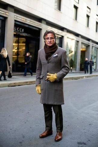 Mode für Herren ab 50 2020: Etwas Einfaches wie die Wahl von einem grauen Mantel und einer dunkelgrünen Anzughose kann Sie von der Menge abheben. Braune Leder Oxford Schuhe sind eine großartige Wahl, um dieses Outfit zu vervollständigen.