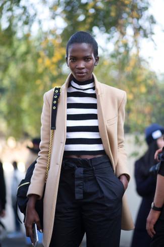 beige Mantel, weißer und schwarzer horizontal gestreifter kurzer Pullover, schwarze Karottenhose, schwarze Segeltuch Umhängetasche für Damen