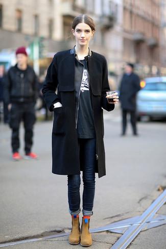Wie kombinieren: schwarzer Mantel, schwarze Leder Bikerjacke, schwarzes und weißes bedrucktes T-Shirt mit einem Rundhalsausschnitt, dunkelblaue enge Jeans
