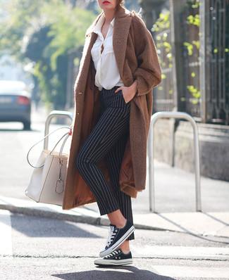Wie kombinieren: brauner Mantel, weiße Bluse mit Knöpfen, schwarze und weiße vertikal gestreifte enge Hose, schwarze und weiße Segeltuch niedrige Sneakers
