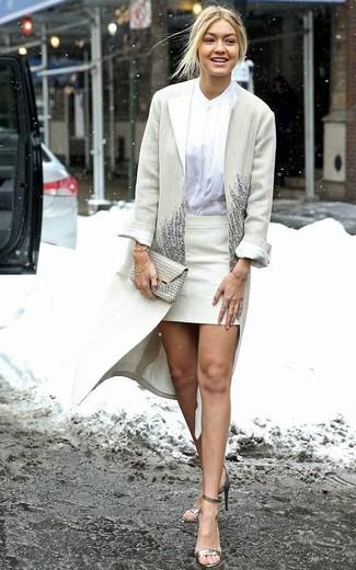 Wie kombinieren: hellbeige Mantel, weiße Bluse mit Knöpfen, hellbeige Minirock, goldene Leder Sandaletten