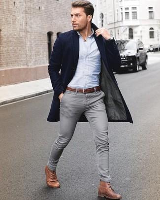 Wie kombinieren: dunkelblauer Mantel, hellblaues Businesshemd, graue enge Jeans, braune Lederformelle stiefel