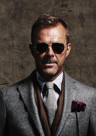 Lalle Johnson trägt grauer Mantel, graues Businesshemd mit Karomuster, graue Strick Krawatte, dunkellila Einstecktuch