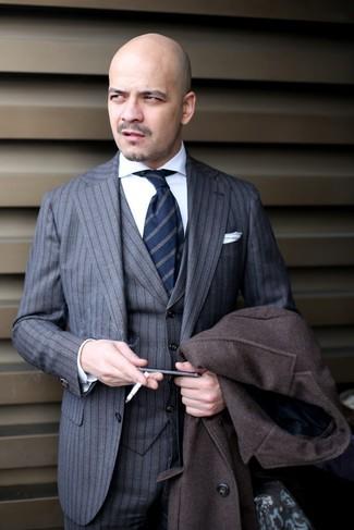 Wie kombinieren: dunkelbrauner Mantel, grauer vertikal gestreifter Dreiteiler, weißes Businesshemd, dunkelblaue vertikal gestreifte Krawatte