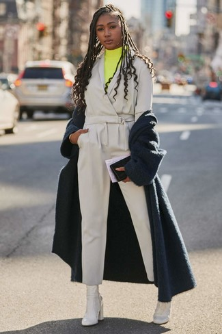 Wie kombinieren: dunkelblauer flauschiger Mantel, gelber Rollkragenpullover, grauer Jumpsuit, weiße Leder Stiefeletten