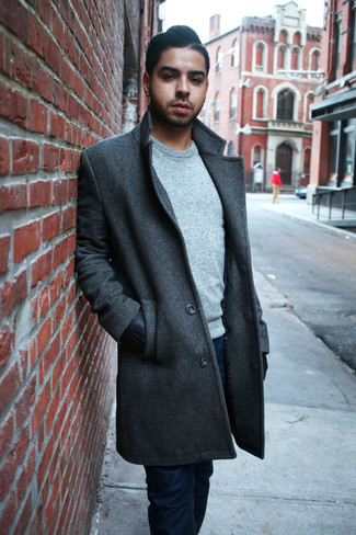 Wie kombinieren: dunkelgrauer Mantel, grauer Pullover mit einem Rundhalsausschnitt, dunkelblaue Jeans, schwarze Lederhandschuhe