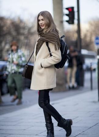 Wie kombinieren: hellbeige Mantel, schwarze Leder enge Jeans, schwarze Leder mittelalte Stiefel, schwarzer Leder Rucksack