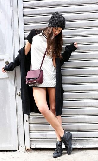 Wie kombinieren: schwarzer Mantel, weißes und schwarzes gestepptes Etuikleid, schwarze hohe Sneakers aus Leder, lila beschlagene Leder Umhängetasche