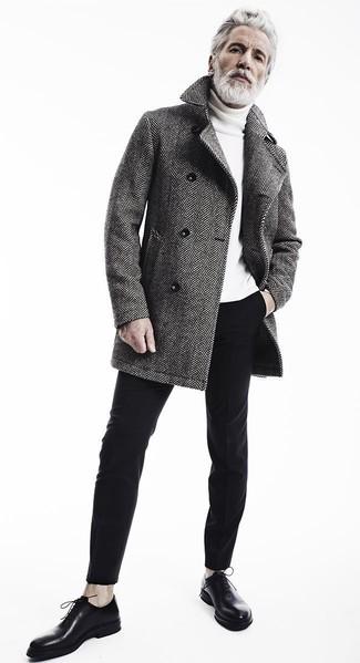 Aiden Shaw trägt grauer Mantel mit Fischgrätenmuster, weißer Rollkragenpullover, schwarze Chinohose, schwarze Leder Oxford Schuhe