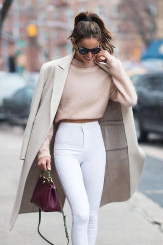 Wie kombinieren: hellbeige Mantel, hellbeige kurzer Pullover, weiße enge Jeans, lila Leder Umhängetasche