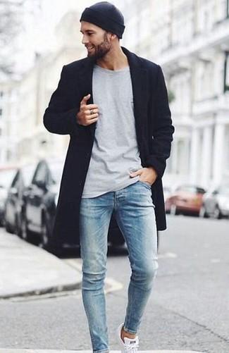 Wie kombinieren: schwarzer Mantel, graues Langarmshirt, hellblaue enge Jeans, weiße niedrige Sneakers
