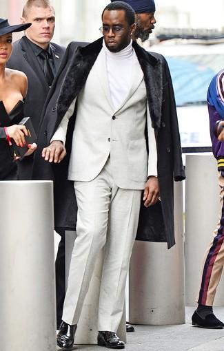 Wie kombinieren: schwarzer Mantel mit einem Pelzkragen, hellbeige Anzug, weißer Rollkragenpullover, schwarze Chelsea-Stiefel aus Leder