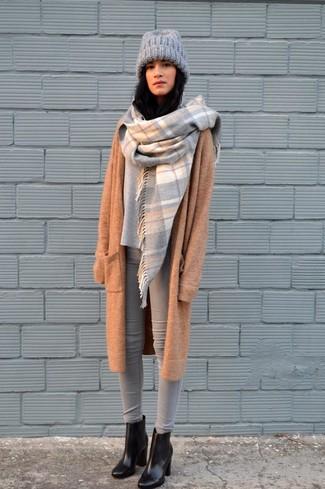 Wie kombinieren: beige Strick Mantel, grauer Oversize Pullover, graue enge Jeans, schwarze Leder Stiefeletten