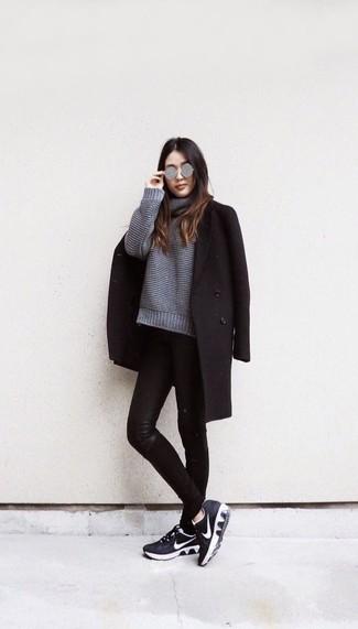 Wie kombinieren: schwarzer Mantel, grauer Strick Oversize Pullover, schwarze Leder enge Jeans, schwarze und weiße Sportschuhe