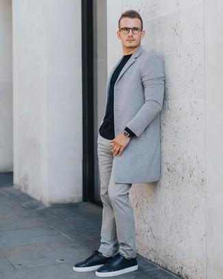 Wie kombinieren: grauer Mantel, schwarzer Pullover mit einem Rundhalsausschnitt, graue Wollanzughose, schwarze Leder niedrige Sneakers