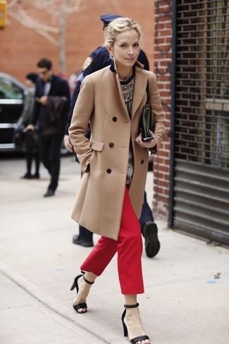 Wie kombinieren: beige Mantel, schwarzer bedruckter Pullover mit einem Rundhalsausschnitt, rote Chinohose, schwarze Leder Sandaletten