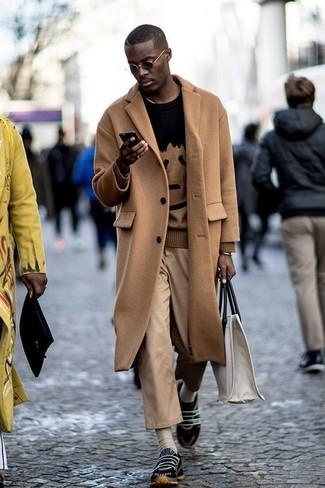 Wie kombinieren: camel Mantel, schwarzer bedruckter Pullover mit einem Rundhalsausschnitt, beige Chinohose, schwarze Sportschuhe