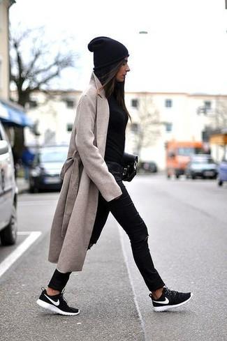 Wie kombinieren: hellbeige Mantel, schwarzer Pullover mit einem Rundhalsausschnitt, schwarze enge Jeans mit Destroyed-Effekten, schwarze und weiße Sportschuhe