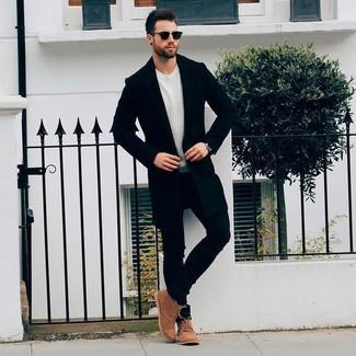 Wie kombinieren: schwarzer Mantel, hellbeige Pullover mit einem Rundhalsausschnitt, schwarze enge Jeans, braune Chukka-Stiefel aus Wildleder