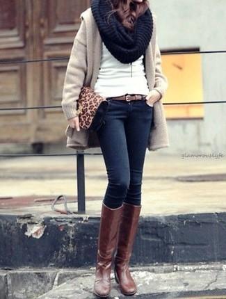 Wie kombinieren: hellbeige Mantel, weißer Pullover mit einem Rundhalsausschnitt, dunkelblaue enge Jeans, braune kniehohe Stiefel aus Leder