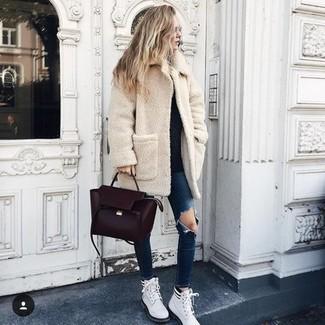 Wie kombinieren: hellbeige Fleece-Mantel, schwarzer Pullover mit einem Rundhalsausschnitt, dunkelblaue enge Jeans mit Destroyed-Effekten, weiße flache Stiefel mit einer Schnürung aus Leder