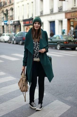 dunkeltürkiser Mantel, hellbeige Pullover mit einem Rundhalsausschnitt mit Leopardenmuster, schwarze enge Jeans, schwarze niedrige Sneakers für Damen