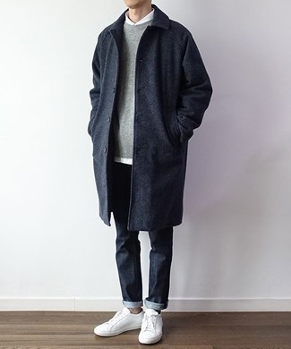 Grauen Pullover mit einem Rundhalsausschnitt kombinieren: trends 2020: Kombinieren Sie einen grauen Pullover mit einem Rundhalsausschnitt mit dunkelblauen Jeans für ein bequemes Outfit, das außerdem gut zusammen passt. Komplettieren Sie Ihr Outfit mit weißen Leder niedrigen Sneakers.