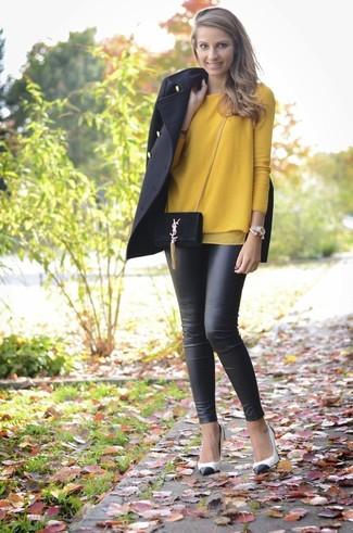 Wie kombinieren: schwarzer Mantel, senf Pullover mit einem Rundhalsausschnitt, schwarze Lederleggings, weiße und schwarze Leder Pumps