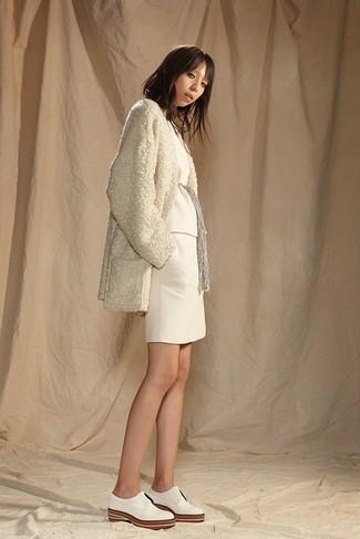 Wie kombinieren: hellbeige Fleece-Mantel, weißer Pullover mit einem Rundhalsausschnitt, weißer Strick Minirock, weiße Leder Oxford Schuhe