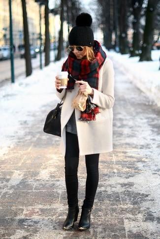 Hellbeige Mantel kombinieren – 10 Winter Damen Outfits: Probieren Sie diese Kombi aus einem hellbeige Mantel und schwarzen engen Jeans, umeinen legeren Look zu erreichen, der in der Garderobe der Frau nicht fehlen darf. Ergänzen Sie Ihr Look mit schwarzen Leder Stiefeletten. Was für eine tolle Winter-Look Idee!