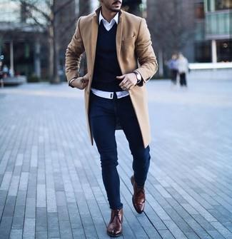 Wie kombinieren: camel Mantel, dunkelblauer Pullover mit einem V-Ausschnitt, weißes Langarmhemd, dunkelblaue enge Jeans