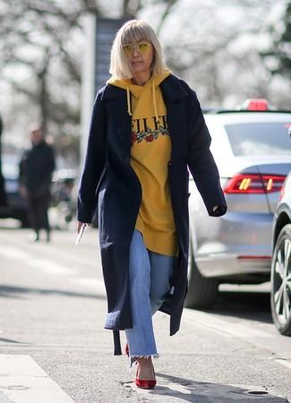 Wie kombinieren: dunkelblauer Mantel, gelber bedruckter Pullover mit einer Kapuze, hellblaue Jeans, rote Wildleder Pumps