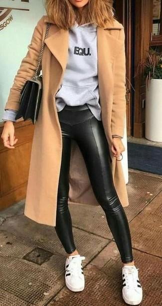Wie kombinieren: beige Mantel, grauer bedruckter Pullover mit einer Kapuze, schwarze Lederleggings, weiße und schwarze Leder niedrige Sneakers
