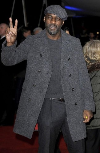 Idris Elba trägt Dunkelgrauer Mantel, Dunkelgrauer Pullover mit Rundhalsausschnitt, Dunkelgraue Wollanzughose, Dunkelgraue Schiebermütze